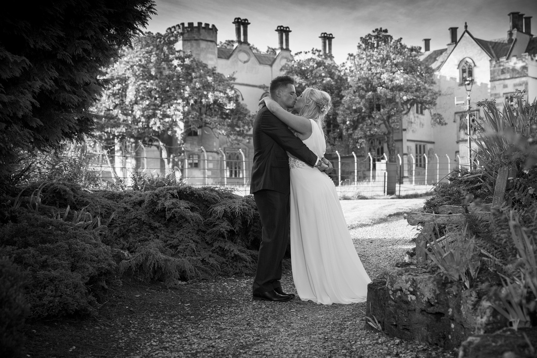 Bride and Groom kissing in front of Ashton Court