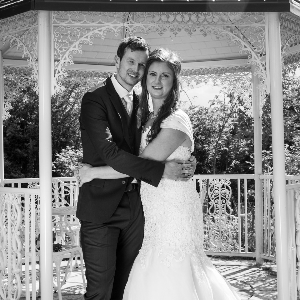 bride & groom by gazebo at great tythe barn tetbury