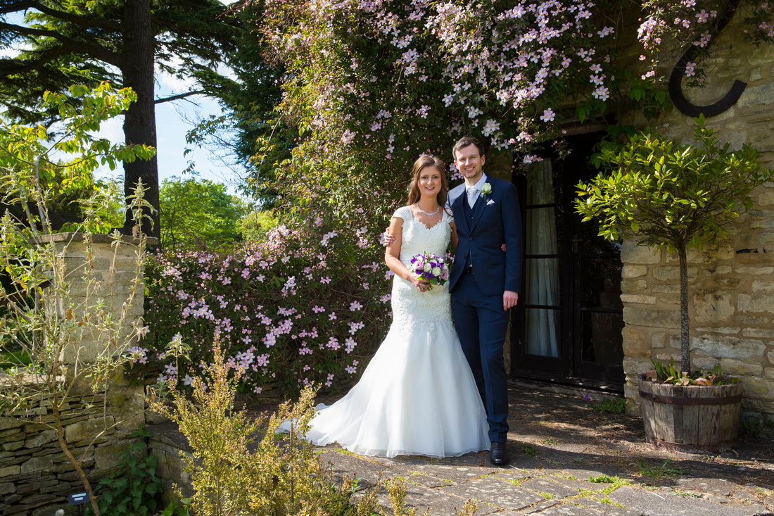 bride and groom by cottage at great tythe barn tetbury