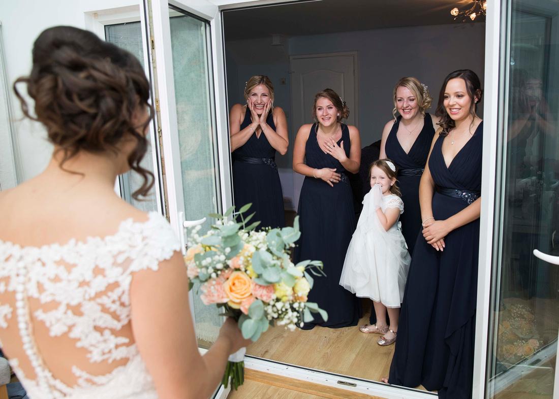 bridesmaids first look at wedding dress