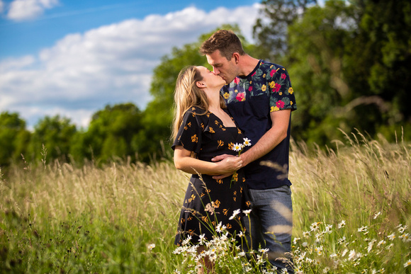 Portrait of couple kissing in fields with blue skies