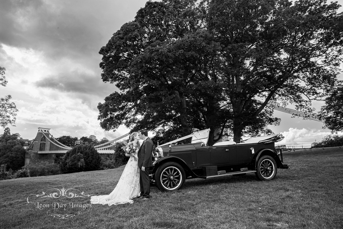 Bride and groom kissing in front of Buick vintage car by Clifton Suspension Bridge Bristol