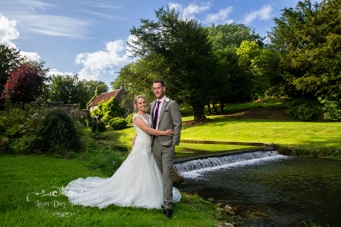 Bride and groom by river cottage at Ston Easton Park on wedding day