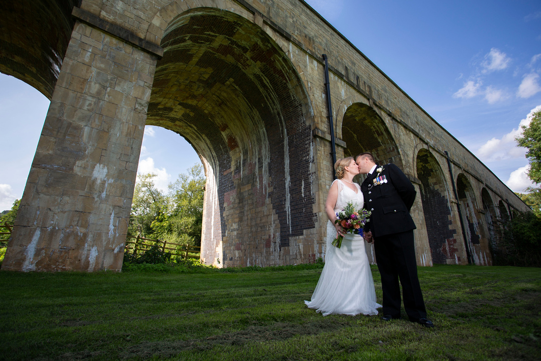 bride kissing policeman groom on field in front of viaduct at limpley stoke in monkton combe