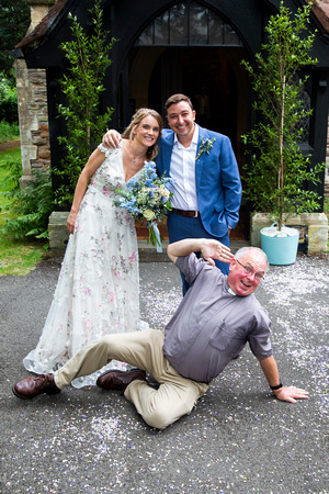 Vicar doing funny pose with bride and groom