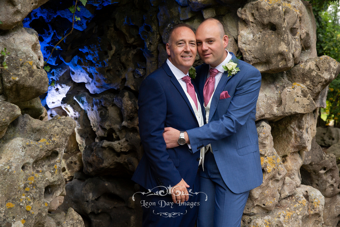 Grooms hugging in grotto of gardens at Bath Spa Hotel