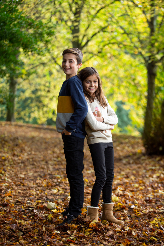 Brother and sister smiling in park with autumn leaves