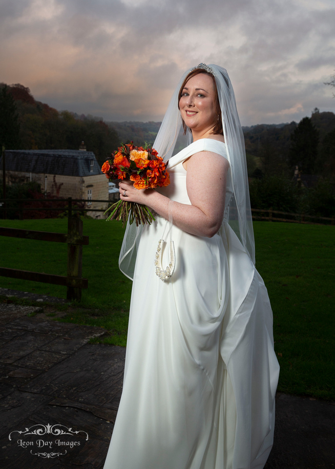 Bride holding bouquet in Limpley Stoke Hotel garden at sunset