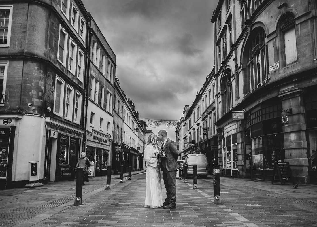 Bride and groom kiss in Cheap Street in Bath after wedding
