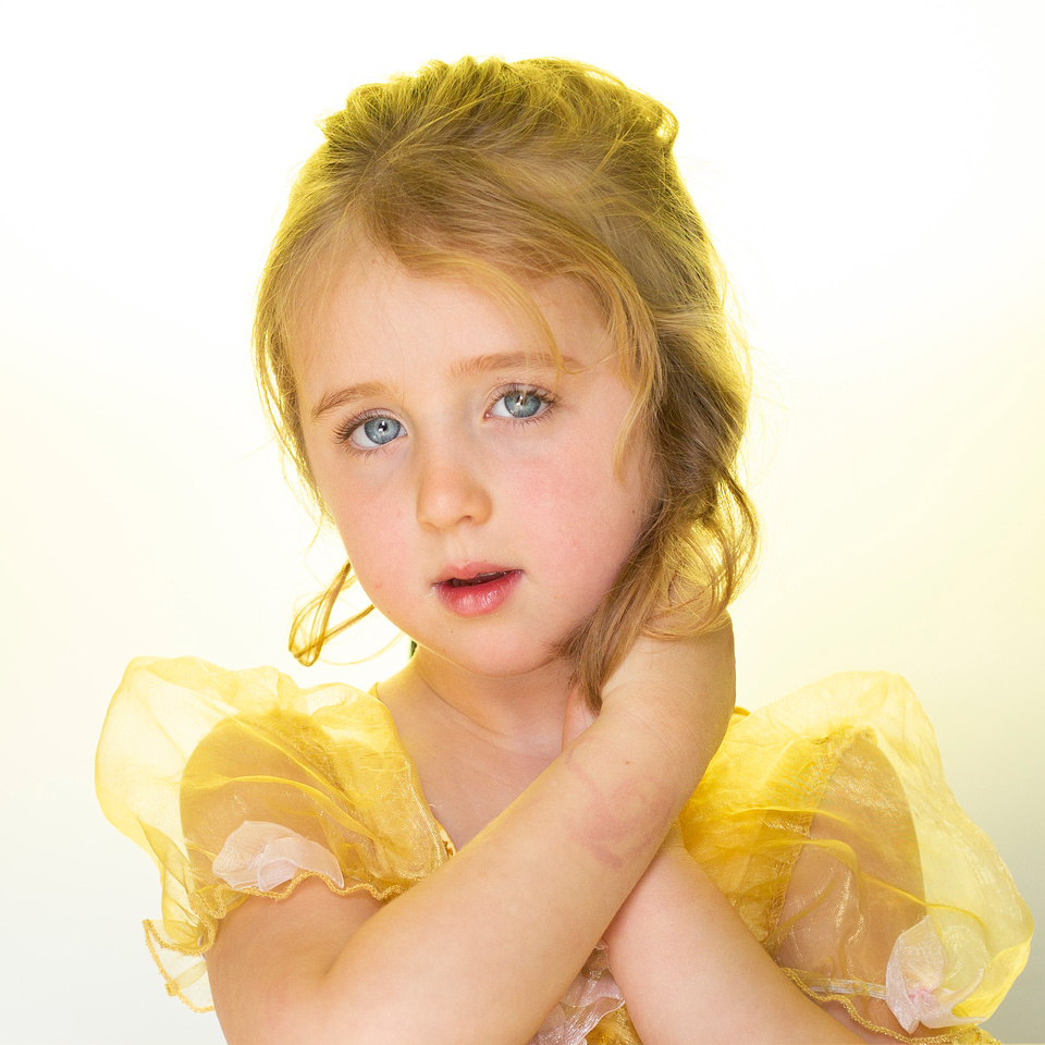 Beautiful girl in Belle princess costume with yellow light and blue eyes