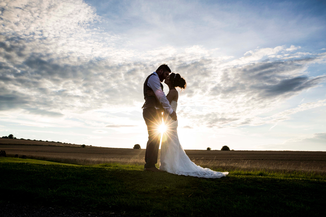 Bride and groom kissing in fields at sunet at Wellington Barn