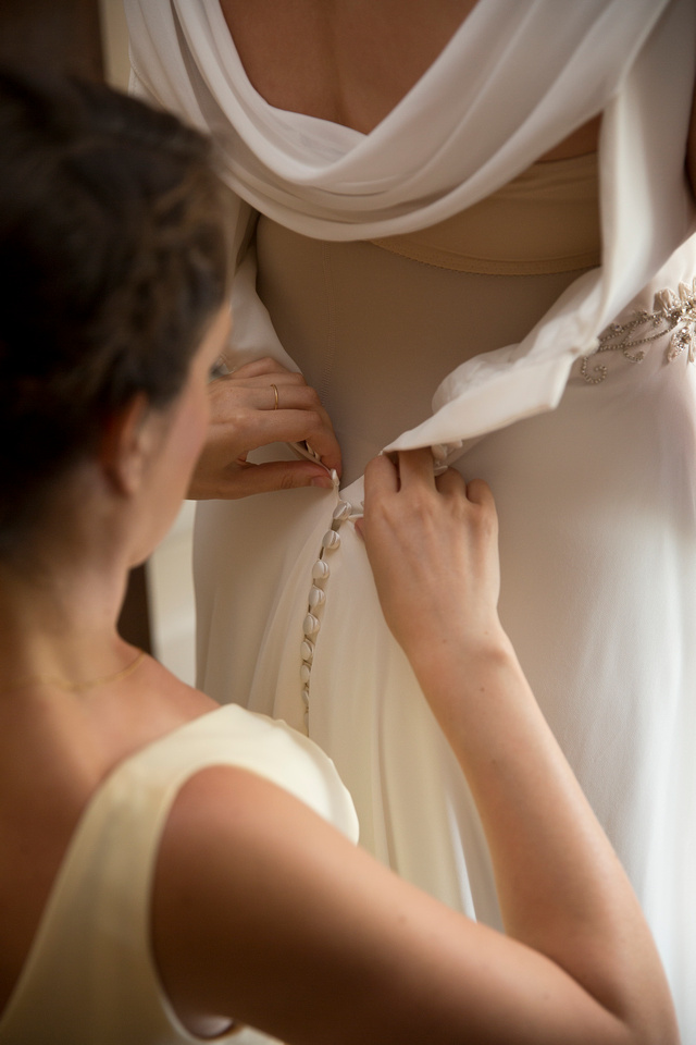 Bridesmaids helping with the wedding dress