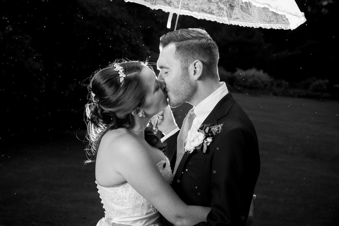 kiss under umbrella in rain homewood park