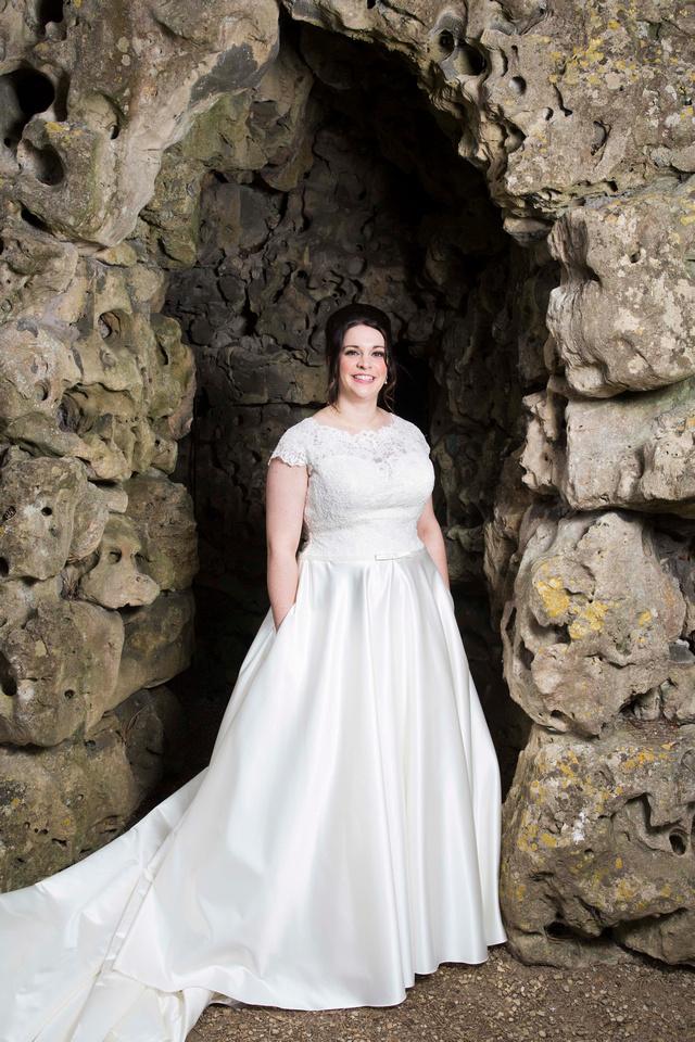 Bride models dress with pockets at the stone arches at Macdonald Bath Spa Hotel