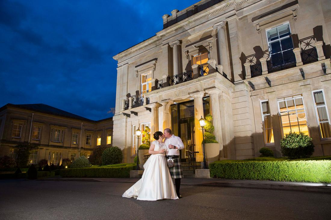 Bride & groom kiss outside Macdonald Bath Spa Hotel at night