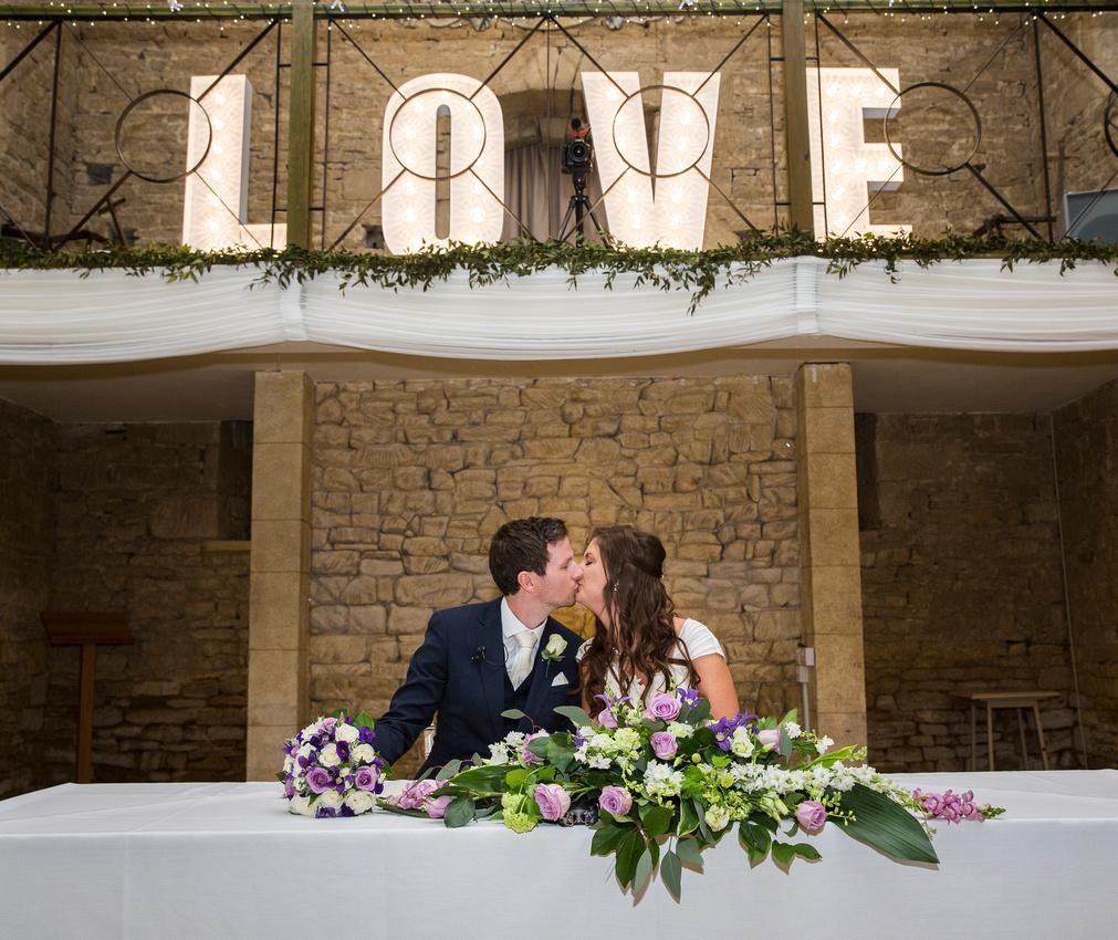 newlyweds bride and groom kiss great tythe barn tetbury