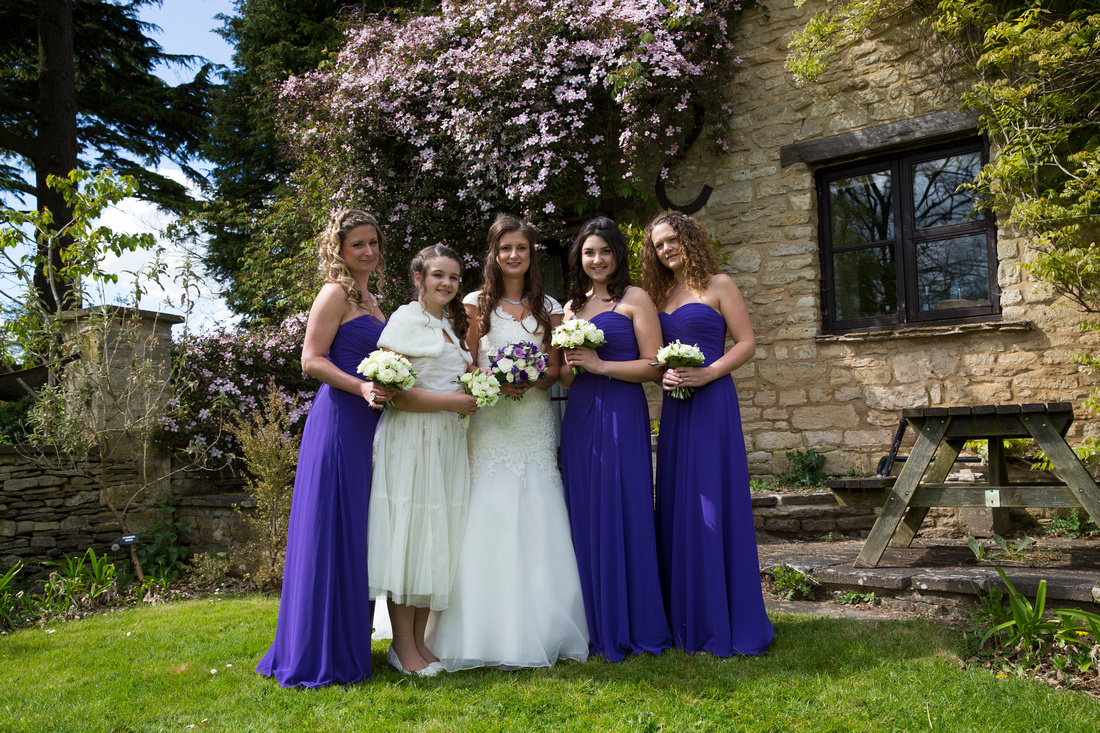 Bride, bridesmaids and flower girl at great tythe barn tetbury cottages