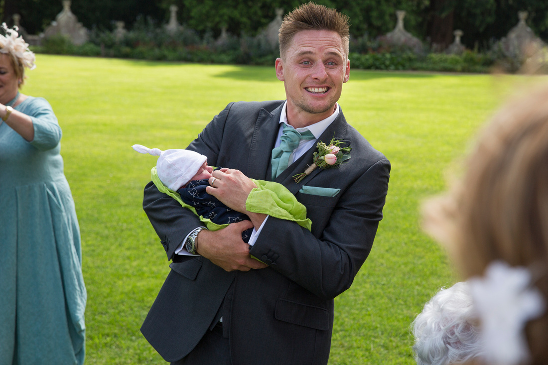 groom with baby ashton court mansion
